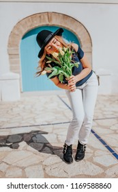Young pretty woman with hat holding yellow tulips in her hands and joking and smiling