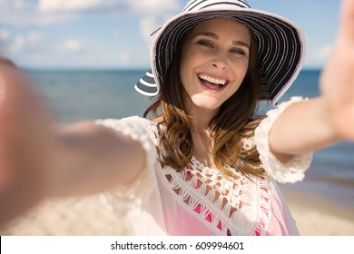 Young pretty woman in hat reaching out her hands