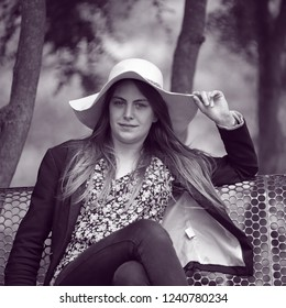 Young and pretty woman with a hat sitting on a bench in a french public park