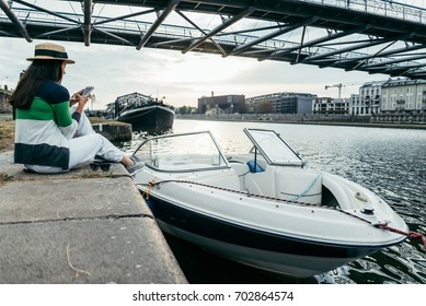 young pretty woman in hat sitting on pier in the morning near boat and taking picture on her phone