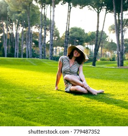 young pretty woman in hat sitting on green grass, happy smiling lifestyle people concept