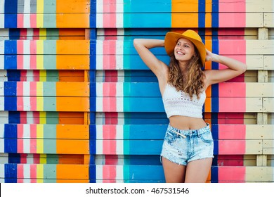 young pretty woman with hat standing and smiling over a colorful background in the summer time