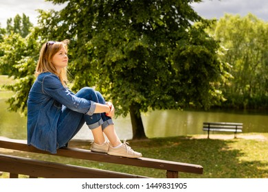 Young pretty woman have a rest in a park. Outdoor relaxing