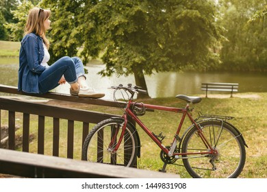 Young pretty woman have a rest in a park after bike ride. Outdoor relaxing