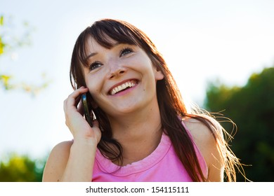 Young pretty woman having a joyful mobile phone conversation and smiling in a sunny day outdoors.