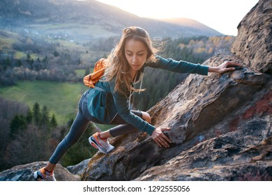 young pretty woman hiker climbed on the cliff and looks confused