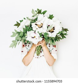 Young pretty woman hold white peony flowers bouquet on white background. Summer floral composition.