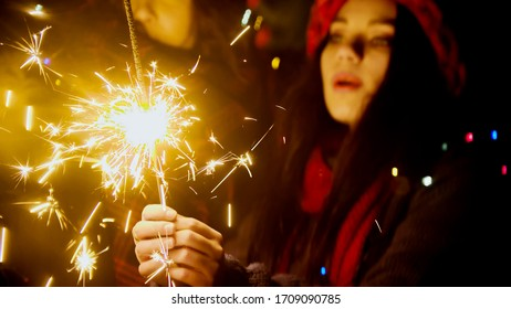Young pretty woman holding bright sparkler at night outdoors