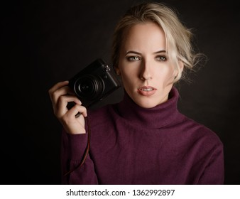 Young pretty woman holding camera over dark background.