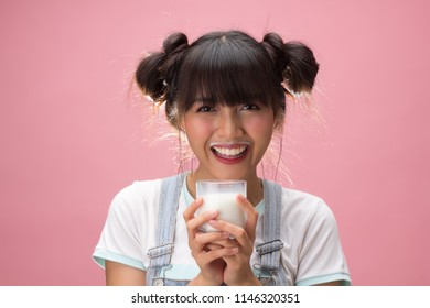 Young pretty woman holding a glass of milk with happiness