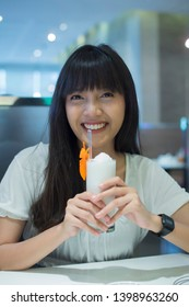 Young pretty woman holding a glass of fresh coconut water frappe with happiness in restaurant
