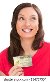 Young pretty woman holding golden plastic bank card and planning her spending