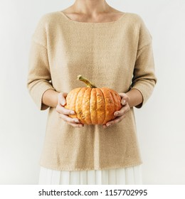 Young pretty woman holding halloween pumpkin on white background. Fall autumn concept.
