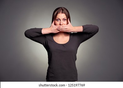 young pretty woman holding hands over her mouth over grey background
