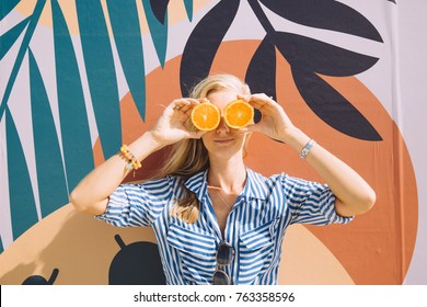 Young pretty woman holding oranges in front of her eyes