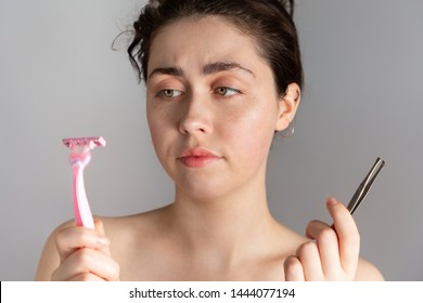 A young pretty woman holding a pair of tweezers and a razor, not knowing how to remove excess hair on her face.The concept of getting rid of unwanted hair