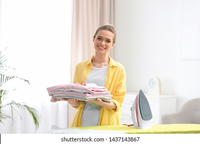 Young pretty woman holding stack of clean laundry at ironing board indoors
