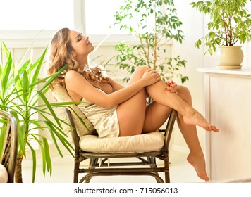 Young pretty woman at home sitting on modern chair in front of window relaxing at her living room. Morning. Portrait of a girl relaxing at home