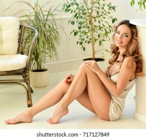Young pretty woman at home sitting on the floor relaxing at her living room. Morning. Portrait of a girl relaxing at home