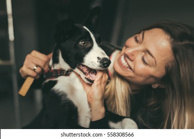 Young pretty woman hugging her cute dog, border collie puppy. Shallow depth of field.