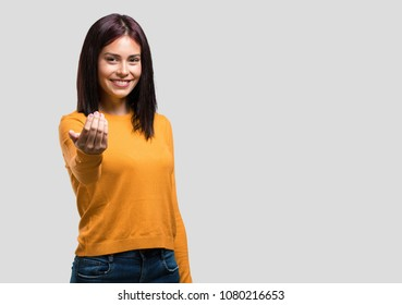 Young pretty woman inviting to come, confident and smiling making a gesture with hand, being positive and friendly