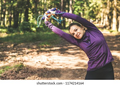 Young pretty woman jogging and making exercises in the sunny forest