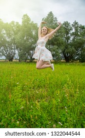 A young pretty woman is jumping in a meadow in the air