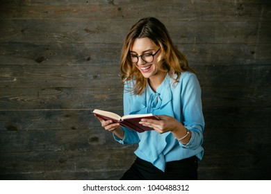 Young pretty woman laughing while reading a book, in eyeglasses. Dressed in blouse