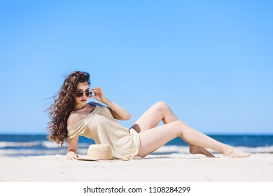 A young pretty woman laying on the beach, wearing sunglasses. Sunbathing.