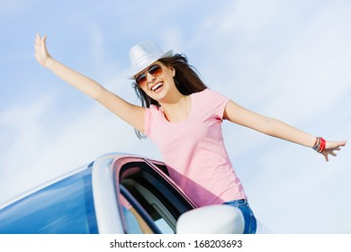 Young pretty woman leaning out of car window