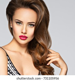 Young pretty woman with long hair. Closeup portrait with a pretty face of the young girl. Fashion model with red lips posing at studio in black dress.