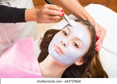 Young pretty woman looking at camera while laying on couch being treated by cosmetologist applying blue cosmetology mask to her face