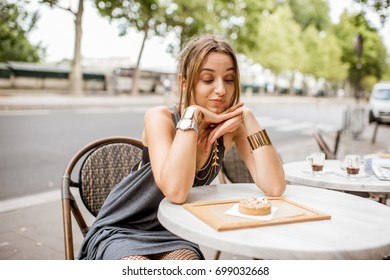 Young pretty woman looking at the sweet cake sitting outdoors at the french cafe