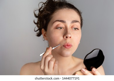 A young pretty woman looks in a compact mirror and pulls out her antennae with tweezers. The concept of getting rid of unwanted hair