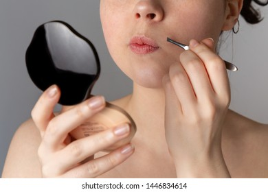 A young pretty woman looks in a compact mirror and pulls out her antennae with tweezers. The concept of getting rid of unwanted hair. Close up