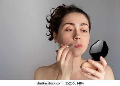 A young pretty woman looks in a compact mirror and pulls out her antennae with tweezers. The concept of getting rid of unwanted hair. Copy space