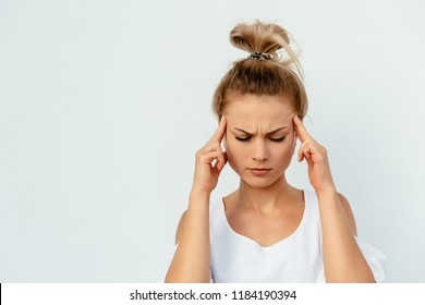 Young pretty woman looks tired, having a headache, dizzy, touching her temples while closing eyes. Isolated on white background.