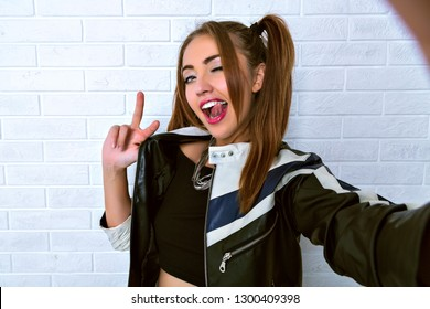 Young pretty woman making selfie over brick wall, winking showing peace gesture and her tongue, wearing racer leather jacket and two playful ponytails.