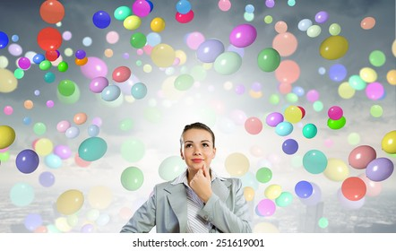Young pretty woman and many colorful balloons around
