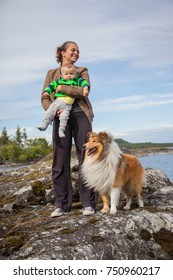 Young pretty woman is mother of cute baby boy who is she holding in hands, hugging him. Beautiful rough collie dog is standing with them, accompanying in a camping trip in north Russia, Karelia