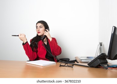 Young pretty woman in the office talking on the phone, wearing red jacket, looking left
