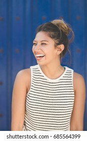 Young pretty woman on blue background looking away laughing