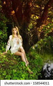 Young pretty woman on the forest lake