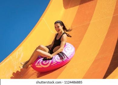 Junge schöne Frau auf dem aufblasbaren Ring, die Spaß auf der orangefarbenen Wasserrutsche im Aquapark hat.Sommerurlaub. Wochenende im Resort