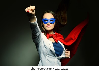 Young pretty woman opening her shirt like a superhero. Super girl, image toned. Beauty saves the world.