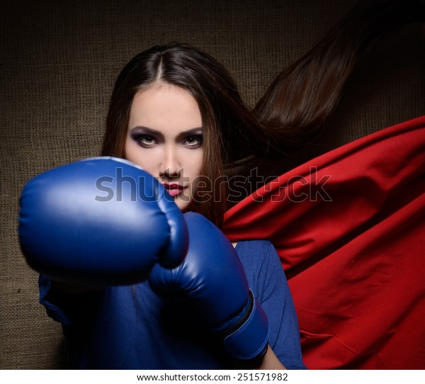 Young pretty woman opening her t-shirt like a superhero. Super girl, image toned. Beauty saves the world.