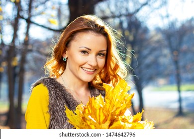 Young pretty woman in the park in autumn