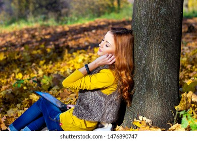 Young pretty woman in the park listening music in autumn. woman in the park with tablet in autumn day. woman in the park with laptop in autumn day