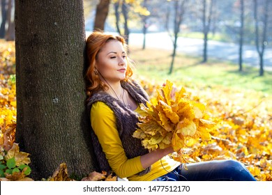 Young pretty woman in the park listening music in autumn