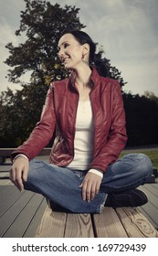 Young pretty woman in park sitting in lotus position